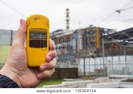radiometer in hand with fourth Chernobyl reactor on the background