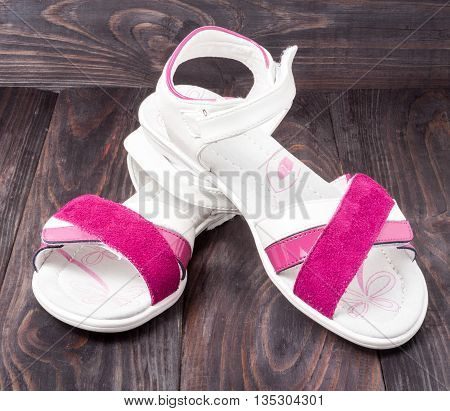 child's sandals on a dark wooden background.