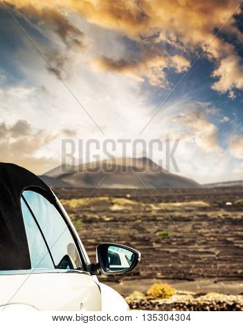 car on offroad by mountain at sunset