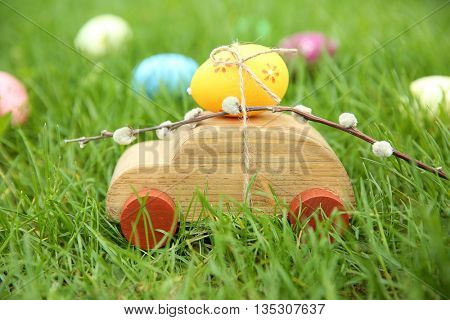Decorative toy car with pussy willow and Easter egg on green grass