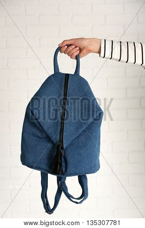 Woman hand holding backpack on grey background