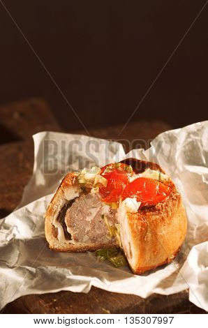 Pork pie on rustic wooden board with slice taken out