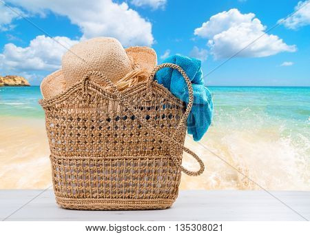 Beach basket packed with towel and sunhat with beach blur background