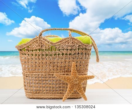 Beach bag with towel with ocean blur background