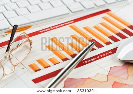 Business workplace with keyboard glasses and financial documents on table