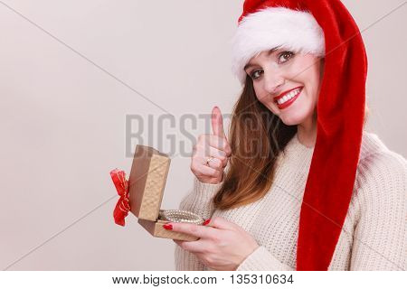 Christmas girl with small gift. Young woman holding ribon box wearing santa cap. Celebration leisure relax holidays concept.