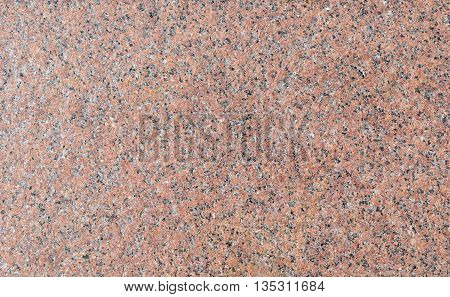 Surface of the wall with light pink granite with brown gray and white patches.