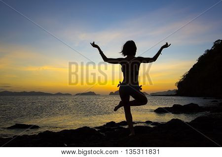 girl in a yoga pose meditating at sunset