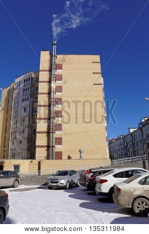 Nizhny Novgorod Russia. - March 18.2016. Modern multi-story brick apartment house with its own boiler. In recent cold days in early spring boiler heats the house.