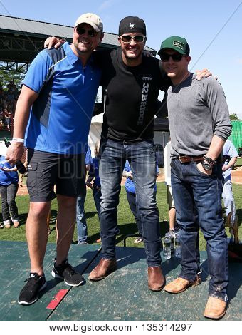 ARLINGTON, TX - APR 18: (L-R) Storme Warren, Luke Bryan and Justin Moore at the ACM & Cabelaâ??s Great Outdoor Archery Event at the Texas Rangers Youth Ballpark on April 18, 2015.