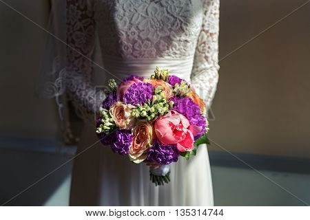 Bouquet of peonies in the hands of bride. Shot with contrasting light.