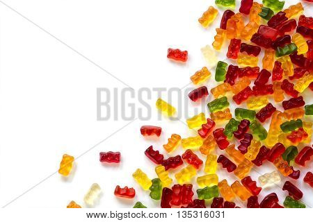 corner background made of colorful fruit gum candies isolated with small shadow on white generous copy space