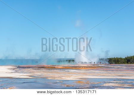 Tourists standing in the steam of Grand Prismatic hot spring