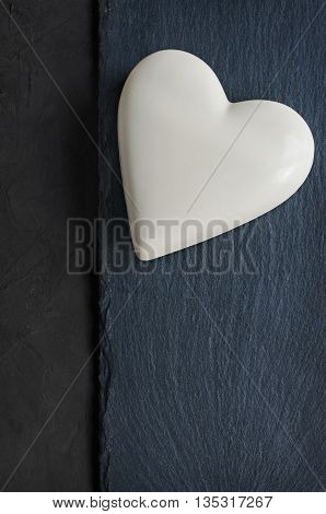 White chocolate heart on black slate background