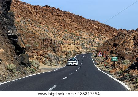 TEIDE, TENERIFE, SPAIN - DECEMBER 5, 2015: Asphalt road to volcano Teide among rocky mountains on Tenerife island, Spain