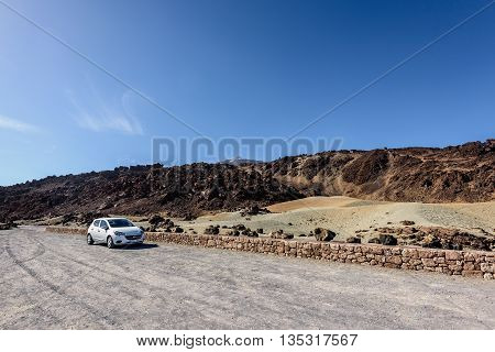 TEIDE, TENERIFE, SPAIN - DECEMBER 2015: Car parking among volcanic hills at Teide National par on Tenerife island, Spain