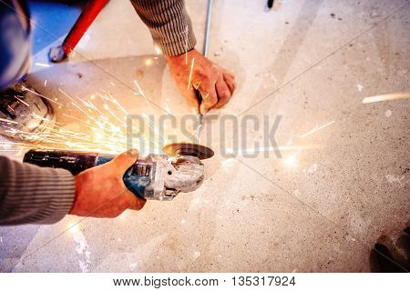 Worker Cutting Steel Bars Using Manual Grinder