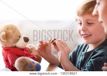 It looks so sweet. Smiling little boy holding a red strawberry while sitting with his mother at the table