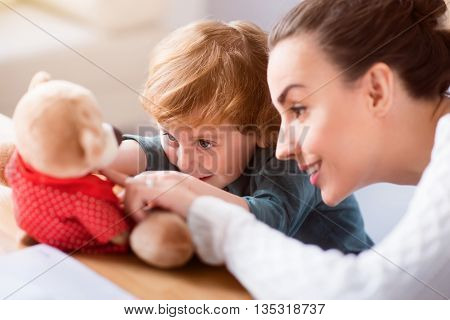 Look here. Little funny boy and his pleasant mother looking attentively at the teddy bear while sitting at the table