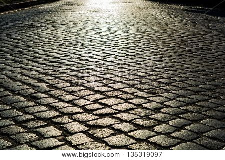 sunlight on cobblestone road in the morning. old stone texture