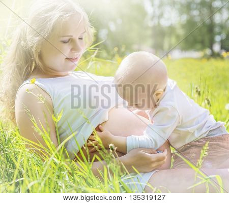 A pregnant woman lies, her little son looks at her belly in a meadow illuminated by sunlight