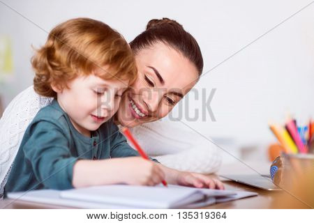 Very nice. Charming smiling mother sitting at the table and teaching her little son drawing