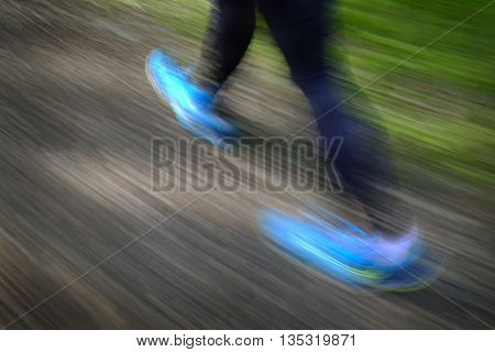 Woman hiking in mountains wilderness fitness exploring blurred feet for movement