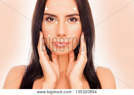 Portrait Of Attractive Girl Touching Her Face With Arrows