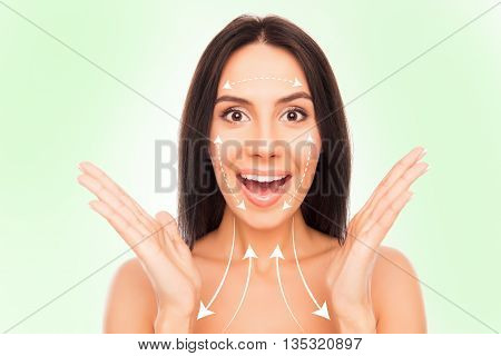 Portrait Of Surprised Pretty Woman With Beautiful Skin And Drawing Arrows On It