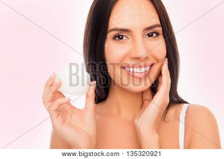 Close-up Photo Of Sensetive Pretty Woman Holding Jar Of Cream And Touching Her Face With Arrows Of E