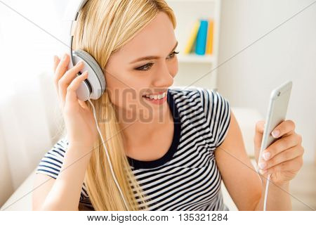 Portrait Of Pretty Cheerful Young Girl Listening Music In Headphones