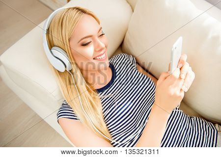 Portrait Of Beautiful Girl Lying On Couch And Listening Music In Headphones