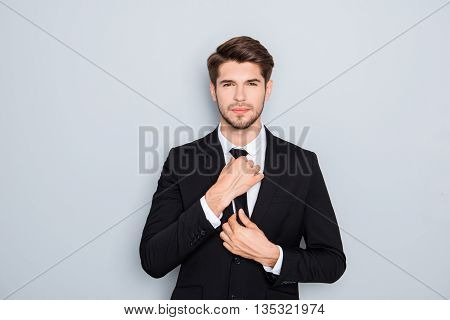 Portrait Of Handsome Businessman Correcting Tie On Gray Background