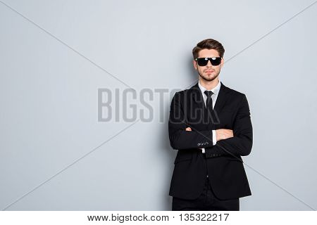 Brutal Man In Suit And Glasses With Crossed Hands On Gray Background