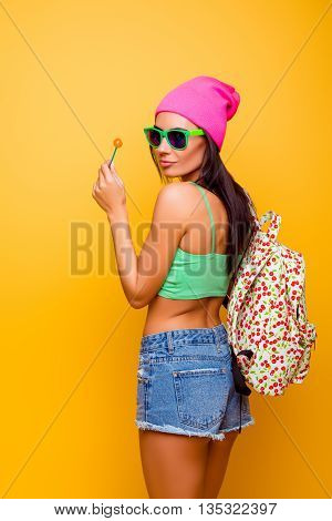 Attractive Cute Hipster  Girl With Backpack Licking Lollypop Standing  Yellow Background