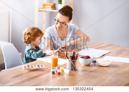 Use this color. Smiling delighted woman opening a jar with the paint while coloring with her son