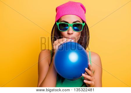 Happy Hipster Girl In Pink Hat Inflating Balloon