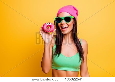 Beautiful Excited Hipster Girl In Pink Hat  Holding Pink Donut On Yellow Wall