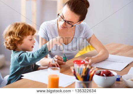 Use this color. Adorable little child taking paint with a brush for making a picture while her mother sitting with him at the table