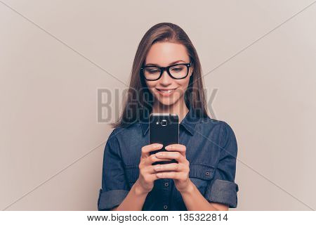 Happy Girl In Glasses Typing Sms On Gray Background