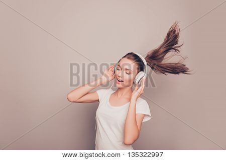 Portrait Of Happy Smiling Girl Listening Music In Headphones And Singing