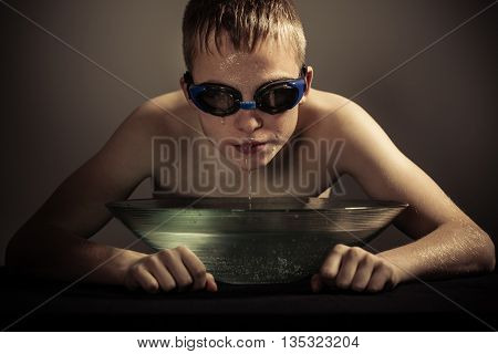 Boy In Goggles With Face Over Bowl Of Water