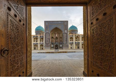 BUKHARA, UZBEKISTAN - MAY 22, 2016: Poi Kalon theological school through the doors of the mosque in Bukhara, Uzbekistan.