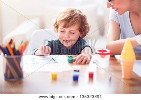 My favorite color. Relaxed little smiling boy holding a brush and painting a picture for her mother