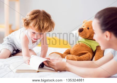 Look here. Smiling nice boy reaching a book while sitting on the bed with his mother