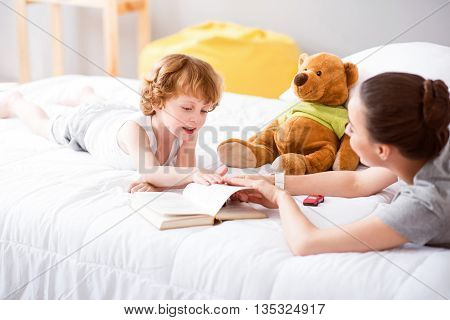 Have a rest. Little amazing child talking to his mother and turning pages in the book while they lying on the bed