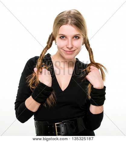 Blonde smiling girl holding her curled hair with both hands. Studio, white background.