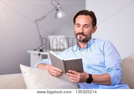 Calm time. Contented mature man sitting on the couch and reading a book