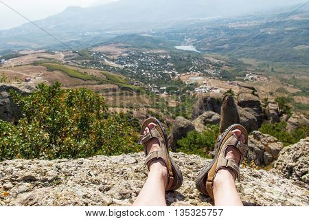 Men in sport sandals lies on the top of Demerdzhi mountain. Close up detail of male feet. Relax after climbing. Crimea Russia.