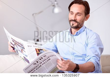 Everything is illuminated. Smiling pleasant middle-aged man reading newspaper while sitting on the sofa
